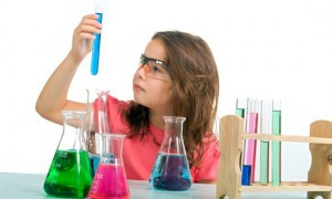 young girl examening a test tube in a science class